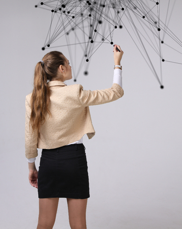 stylus: Worldwide network or wireless internet connection futuristic concept. Young woman working with linked dots on grey background. Stock Photo