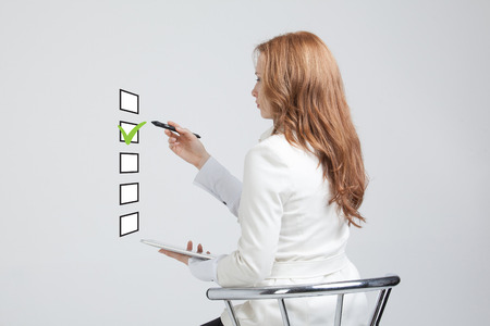 stylus: Young business woman checking on checklist box. Gray background. Concept on the topic of elections