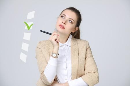 Jonge bedrijfsvrouw die op controlelijstdoos controleert. Grijze achtergrond. Concept over het onderwerp verkiezingen Stockfoto