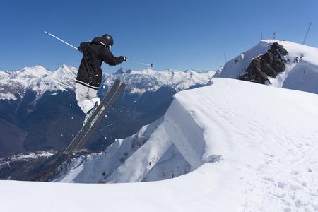 Ski rider jumping on snowy mountains. Extreme ski freeride sport.