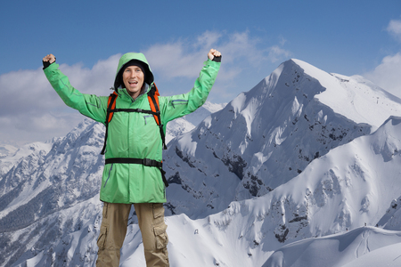 Happy male mountain climber with arms raised above the head. In the background the high mountains. Portrait of a man on the topic of extreme mountaineering and success. Stock Photo