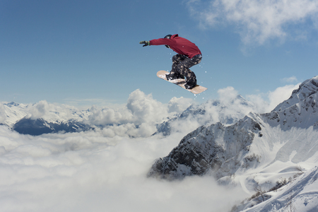 offpiste: Snowboard rider jumping on snowy mountains. Extreme snowboard freeride sport.