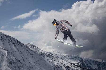 off piste: Snowboard rider jumping on snowy mountains. Extreme snowboard freeride sport.