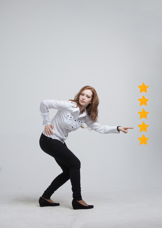 5 star rating or ranking, benchmarking concept on grey background. Woman assesses service, hotel or restaurant Stock Photo