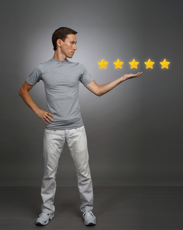 rating: 5 star rating or ranking, benchmarking concept on grey background. Man assesses service, hotel or restaurant Stock Photo