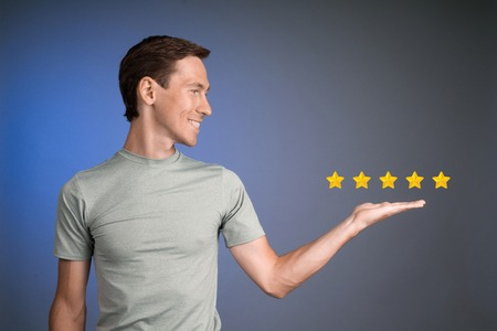 rating: 5 star rating or ranking, benchmarking concept on blue background. Man assesses service, hotel or restaurant.