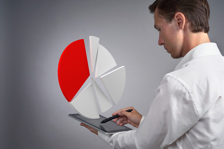 Young man in white shirt working with a pie chart on a tablet computer, application for budget planning or financial statistics.