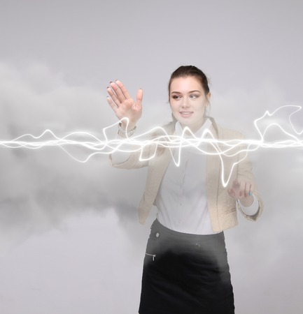 Young woman making magic effect - flash lightning. The concept of electricity, high energy. Stock Photo