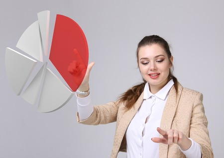 analytic: Young Businesswoman shows a pie chart (circle diagram) on grey background. Business analytics concept.