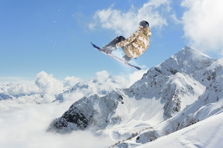 Snowboard rider jumping on mountains above the clouds. Extreme winter sport. Stock Photo