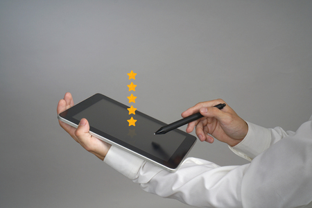 5 star rating or ranking, benchmarking concept on grey background. Man with tablet PC assesses service, hotel or restaurant