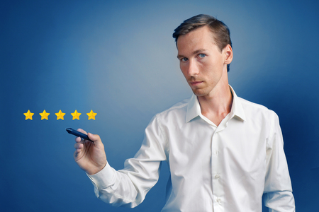 5 star rating or ranking, benchmarking concept on blue background. Man assesses service, hotel or restaurant Stock Photo