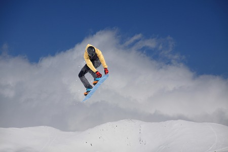 Snowboard rider jumping on mountains. Extreme snowboard freeride sport. Stock Photo