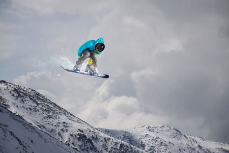 freeride: Flying snowboarder on mountains. Extreme sport.