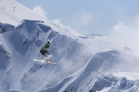 freeride: Jumping snowboarder in winter mountain. Extreme sport.