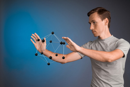 particulate: Young man works on a model of molecule. Stock Photo