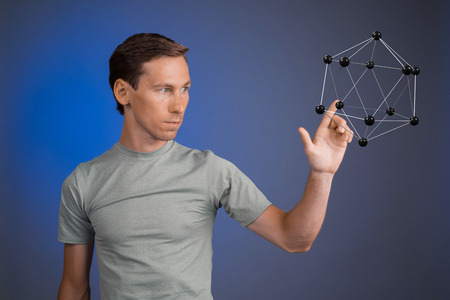 corpuscle: Young man works on a model of molecule. Stock Photo