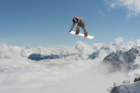 Snowboarder jumps in mountains, winter extreme sport.