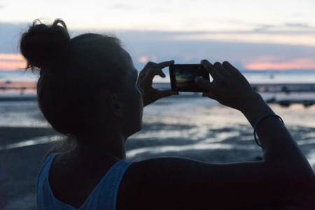 Woman takes a sunset above the sea on a phone camera. photo