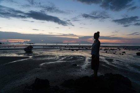 Female silhouette at sunset, woman stands on the sea beach. photo