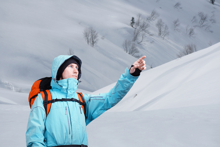 The mountaineer pointing at peak, standing against a winter mountain landscape. Stock Photo