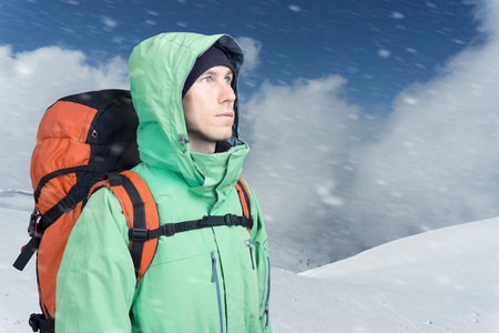 willpower: Man alpinist looks up against a winter mountain landscape. Stock Photo