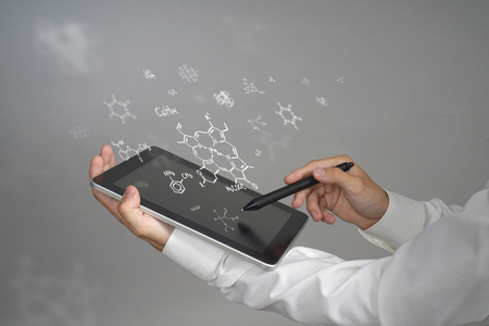 medical drawing: Man scientist with tablet pc and stylus or pen working with chemical formulas on gray background.