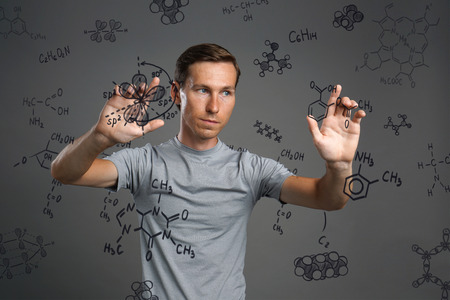 medical drawing: Young man scientist working with chemical formulas on gray background.