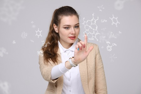 medical drawing: Woman chemist working with chemical formulas on grey background. Stock Photo