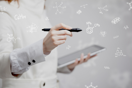 stylus: Woman chemist working with chemical formulas on grey background. Stock Photo