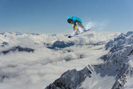 Flying snowboarder on mountains Stock Photo