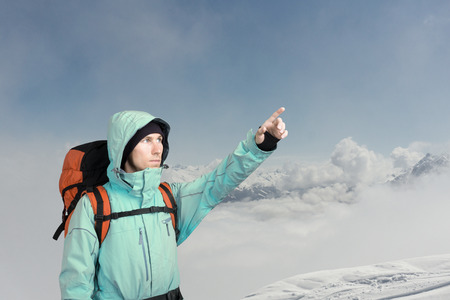 The mountaineer pointing at peak, standing against a winter snowy mountain landscape.