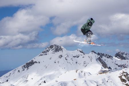 Skier jump in the mountains. Extreme ski sport. Freeride.