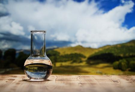 Sauberes Wasser in einer Glaslaborflasche auf Holztisch auf Berghintergrund. Ökologisches Konzept, Prüfung der Reinheit und Qualität des Wassers.
