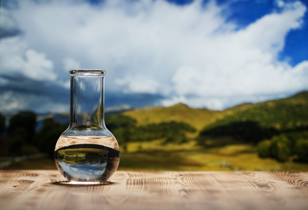 Clean water in a glass laboratory flask on wooden table on mountain background. Ecological concept, the test of purity and quality of water. Stockfoto