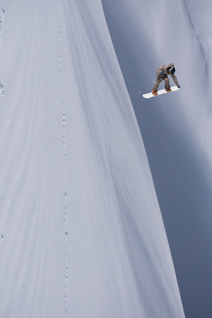 Snowboarder flying on the background of snowy slope. Extreme winter sports, snowboarding. 版權商用圖片