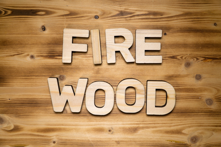 FIREWOOD word made of wooden block letters on wooden board, top view.