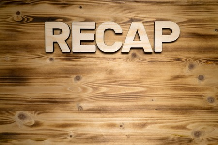 RECAP word made of wooden block letters on wooden board.