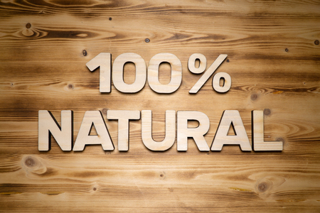 100 percent NATURAL words made of wooden block letters on wooden board.