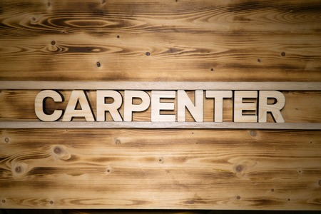 CARPENTER word made of wooden letters on wooden board.