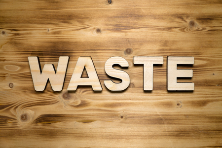 WASTE word made of wooden letters on wooden board