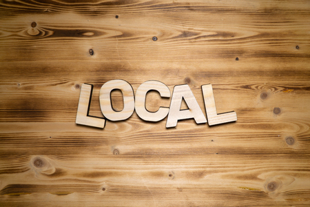 LOCAL word made of wooden letters on wooden board.