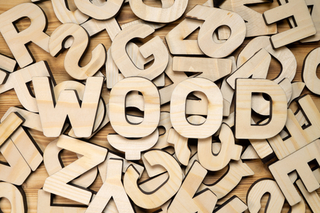 Surface covered with random wooden letters and word WOOD on top.