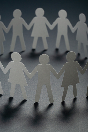 Circle of paper people holding hands on dark surface. Community, union concept. Society and support.