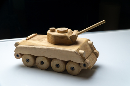 Wood tank on black background. Wooden toy tank studio shot.