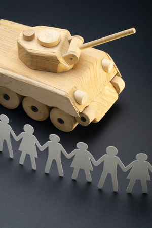 Raw of paper people rallying in front of a tank. Protest, demonstration toy concept. Activism, social movement. Stock Photo