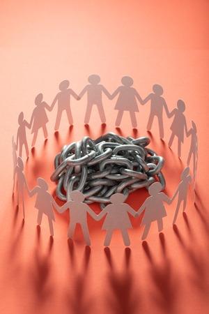 Figuras de papel humano de pie alrededor de una bola de cadena de metal sobre una superficie roja. Libertad, derechos humanos, independencia.