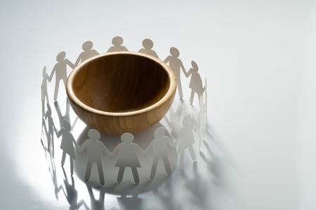 Circle of paper people holding hands in front of big empty bowl. Overpopulation, famine concept. Stock Photo