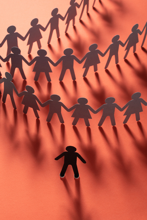 Paper human figure standing in front of paper people holding hands on red surface. Bulling, segregation, conflict concept.