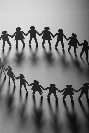 Paper people holding hands on white surface. Community, union concept. Society and support.